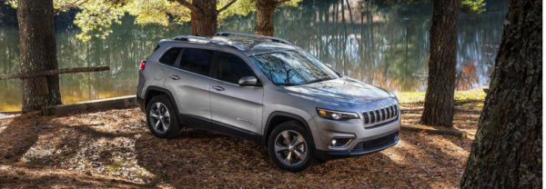 2019 Jeep Cherokee parked under trees by a lake