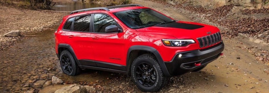 Red 2019 Jeep Cherokee fording a creek